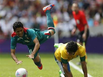 Mexico's Javier Aquino (L) falls over Brazil's Rafael during their men's football gold medal match at Wembley Stadium during the London 2012 Olympic Games August 11, 2012. Foto: Sergio Moraes / Reuters In English