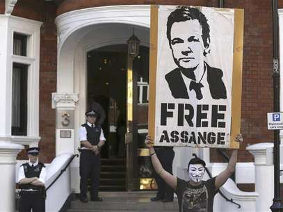 A protestor holds a poster of Wikileaks founder Julian Assange outside Ecuador's embassy in London August 17, 2012. Foto: Neil Hall / Reuters In English