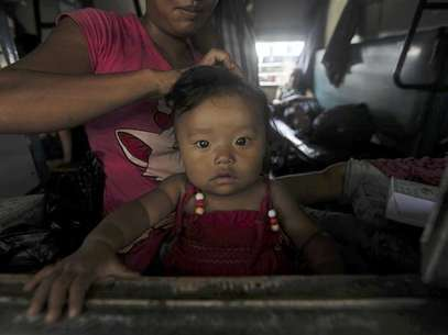 A woman from India's northeastern states ties the hair of her child while sitting inside the train bound for the Assam state at a railway station in Kolkata August 19, 2012. Foto: Rupak De Chowdhuri / Reuters In English