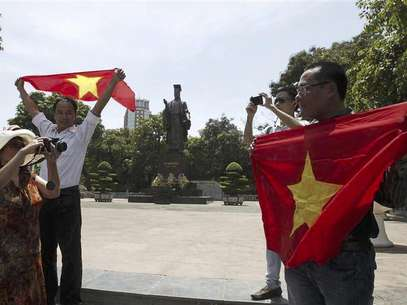 A woman takes a photo of bloggers attending an anti-China protest in Hanoi July 22, 2012. The unlikely alliance between war-hardened farmers and young, urban Internet activists illustrates a rapidly evolving challenge to the Communist government's authority as Vietnamese grow bolder in their protests over issues ranging from land rights to corruption and China's expanding regional influence. Photo taken on July 22, 2012. Foto: Alfonso Le / Reuters In English