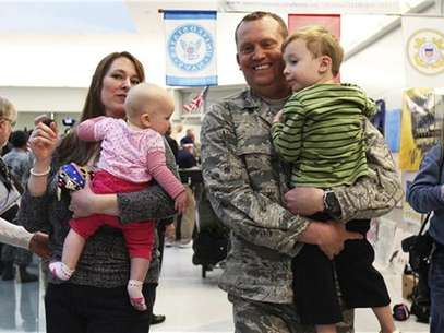 U.S. Air Force airman Lt. Col. Steven Vilpors walks with his wife Joanna and children Connor (R) and Alina (L) as he arrives in Baltimore Washington International Airport, Maryland December 20, 2011. Foto: Shannon Stapleton / Reuters In English