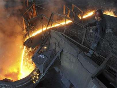 A worker monitors molten iron pouring into a furnace at steel manufacturing plant in Hefei, Anhui province August 15, 2012. Foto: Stringer / Reuters In English