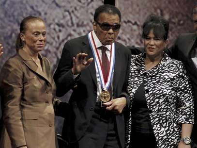 Boxing great Muhammad Ali waves after being awarded the Liberty Medal, as his wife Lonnie (L) and sister-in-law Marilyn Williams (R) look on, at the National Constitution Center in Philadelphia, Pennsylvania September 13, 2012. Ali, retired world heavyweight title holder, received the $100,000 award, sponsored by the nonprofit National Constitution Center, in recognition for his humanitarian efforts and work for civil rights at an awards ceremony on Thursday. Foto: Tim Shaffer / Reuters In English