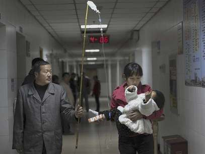 A man uses a stick to hold up a drip for his granddaughter, who is held by her mother, as the girl receives an intravenous injection at a hospital in Hefei, Anhui province, in this November 30, 2011 file picture. Foto: Files / Reuters In English