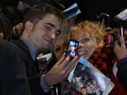 Actor Robert Pattinson poses for a photo with a fan as he arrives for the European premiere of &quot;The Twilight Saga: Breaking Dawn Part 2&quot; in London November 14, 2012. Foto: Luke MacGregor / Reuters