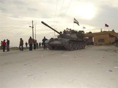 Residents and Free Syrian Army fighters pose near a tank after the fighters said they fought and defeated government troops from the town of Ras al-Ain, near the province of Hasaka, 600 km (375 miles) from Damascus, November 22, 2012. Foto: Samer Abdullah / Reuters