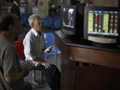 Investors look at computer screens showing stock information at a brokerage house in Shanghai in this June 8, 2012 file photo. Foreign investors have started rebuilding their China equity portfolios, tempted by low valuations after two years of market underperformance and signs economic growth may be stabilizing. They have pumped nearly $4 billion (2 billion pounds) into Chinese equity funds in the past two months alone, trying to get in early on what they hope will be a sustained rally. Picture taken June 8, 2012. Foto: Aly Song / Reuters