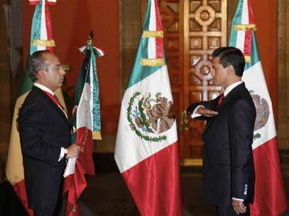 Mexico's outgoing President Felipe Calderon (L) holds the national flag as Mexico's new President Enrique Pena Nieto salutes during a midnight handover ceremony at the Palacio Nacional in Mexico City December 1, 2012. Foto: Presidencia de Mexico / Reuters
