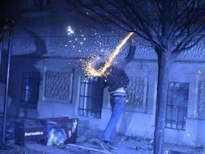 A protester throws fireworks during clashes in Maribor December 3, 2012. Protesters clashed with police in Slovenia's second largest city Maribor on Monday in a demonstration against budget cuts in the financially troubled Alpine state. Police said more than 20 people were arrested in Maribor and at least one policeman was injured after some from a crowd of around 6,000 protesters threw firecrackers, fireworks and rocks. Foto: Srdjan Zivulovic / Reuters