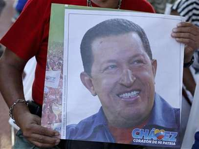A supporter of Venezuelan President Hugo Chavez holds a picture of him, as she attends a mass to pray for Chavez's health in Caracas December 24, 2012. Foto: Carlos Garcia Rawlins / Reuters