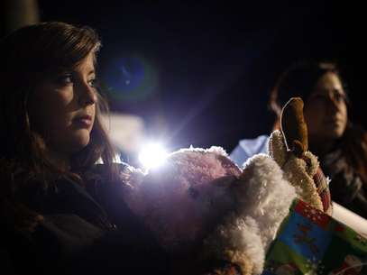 A woman holds stuff animals and Christmas presents at a memorial for the Sandy Hook Elementary School shooting victims in Newtown, Connecticut December 20, 2012. Foto: Joshua Lott / Reuters