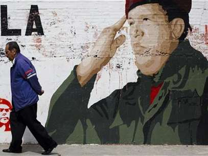 People talk in front of a mural in Caracas January 2, 2013. Venezuelan President Hugo Chavez is aware that his condition is complicated following a fourth cancer operation in Cuba, Vice President Nicolas Maduro said on Tuesday, as the OPEC nation watches for clues to the socialist leader's health. The words read, &quot;Chavez, heart of my country&quot;. Foto: Carlos Garcia Rawlins / Reuters