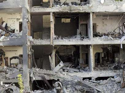 Free Syrian Army fighters and residents are seen near buildings damaged after what activists say were missiles fired by Syrian Air Force fighter jets loyal to Syria's President Bashar al-Assad, in Erbeen, near Damascus January 21, 2013, in this picture provided by Shaam News Network. Foto: Maawia Al-Naser / Reuters