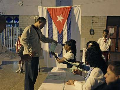 An election official gives a man ballot papers at a special polling station set up in Havana's main train station February 3, 2013. Cubans go to polls to elect National Assembly representatives. Foto: Desmond Boylan (CUBA - Tags: POLITICS ELECTIONS) / Reuters