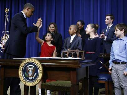 U.S. President Barack Obama high-fives eight-year-old Hinna Zejah after unveiling a series of gun control proposals during an event at the White House in Washington, January 16, 2013. Foto: Jason Reed / Reuters