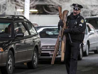 Seattle Police Department Sgt. Paul Gracy carries weapons during a gun buyback event in Seattle, Washington January 26, 2013. Foto: Nick Adams / Reuters