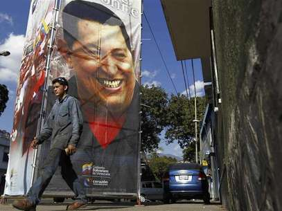 Una persona camina frente a un afiche con la imagen deHugo Chávez. Foto: Carlos Garcia Rawlins / Reuters