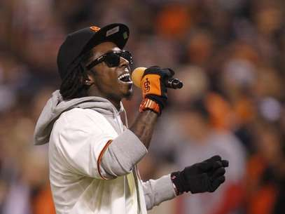 Rapper Lil Wayne sings &quot;Take Me Out To The Ball Game&quot; during the seventh inning stretch in Game 6 of the MLB NLCS playoff baseball series between the St. Louis Cardinals and the San Francisco Giants in San Francisco, October 21, 2012. Foto: Robert Galbraith / Reuters