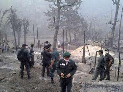 Policiais inspecionam local do incêndio que deixou pelo menos 62 mortos Foto: EFE