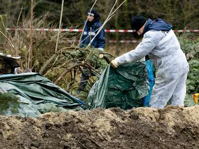 Policias buscam evidências no local onde os restos mortais da vítima foram encontrados Foto: AFP