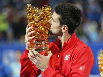 Djokovic beija a taça de mais uma conquista em Abu Dhabi Foto: Reuters