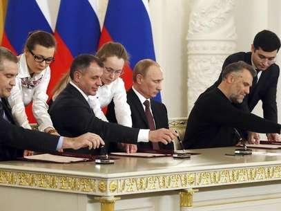 Putin, desafiando protestos ucranianos e sanções ocidentais, assinou nesta terça-feira um tratado anexando a Crimeia à Rússia, mas afirmou não ter planos para controlar outras regiões da Ucrânia Foto: Sergei Ilnitsky / Reuters