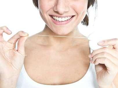 Há quem prefira passar o fio dental antes de escovar os dentes, outros passam depois da escovação, e há, ainda, aqueles que esquecem completamente dessa etapa da higiene bucal. O perigo é deixar acumular restos de alimentos entre os dentes, naqueles espaços tão apertados que só o fio dental consegue chegar. Foto: Shutterstock