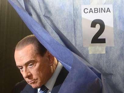 Berlusconi deixa cabina após marcar seus votos em cédula Foto: AFP