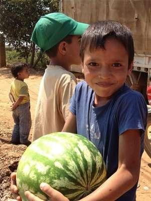 """Ahmed, 10 anos, mal conseguia com o peso de uma melancia que levou correndo para sua casa improvisada no Líbano, onde sabia que a irmã o esperava: """"Estou louco para ver a cara dela quando eu chegar"""" Foto: Divulgação"""