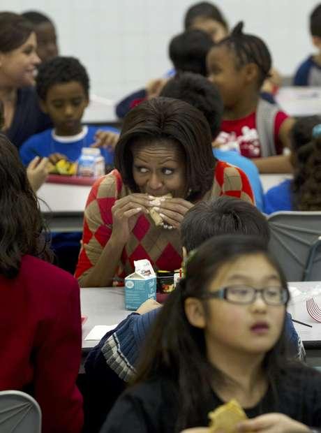 La primera dama Michelle Obama come un taco de pavo junto a varios niños en la escuela primaria Parklawn en Alexandria, Virginia.