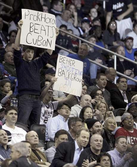 Espectadores muestrasn carteles druante el partido de la NBA entre los Nets de Nueva Jersey y los Sixers de Filadelfia el lunes 23 de abril de 2012. Fue el último partido de los Nets en su arena de Nueva Jersey.