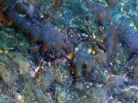 CUARTA SEMANA: Una imagen mejorada de color de una región de Marte cerca de Nili Fossae, que muestra parte del material expulsado de un cráter de impacto, y que contiene algunas de las mejores exposiciones de antiguas capas de roca en Marte.