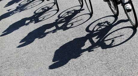 Riders cast shadows as they cycle during the tenth stage of the 99th Tour de France cycling race between Macon and Bellegarde-sur-Valserine, July 11, 2012.