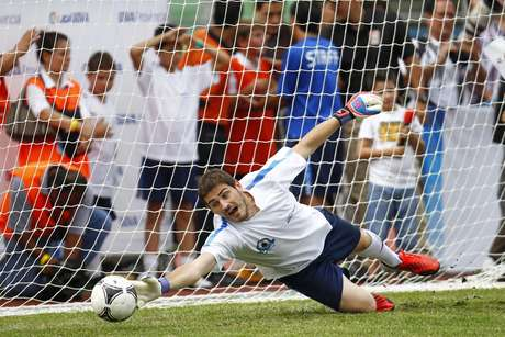 Spain's national soccer team captain Iker Casillas makes a save during a coaching clinic in Caracas July 16, 2012. Casillas is in Venezuela to attend a coaching clinic for children in Caracas. REUTERS/Carlos Garcia Rawlins (VENEZUELA - Tags: SPORT SOCCER)