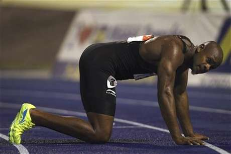 Asafa Powell kneels on the track after their men's 100 meters final event at the Jamaican Olympic trials in Kingston city, June 29, 2012.