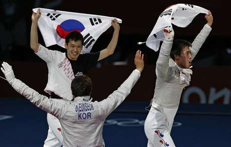 (L-R) South Korea's Bongil Gu, Eunseok Oh and Woo Young Won celebrate with their national flag winning at the end of their men's sabre team gold medal fencing competition against Romania at the ExCel venue at the London 2012 Olympic Games August 3, 2012.
