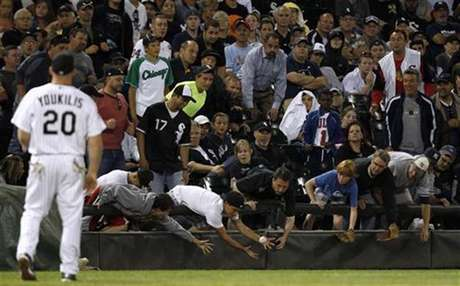 Fans reach for a foul ball during the MLB American League baseball game between Chicago White Sox and New York Yankees, in Chicago, August 20, 2012.