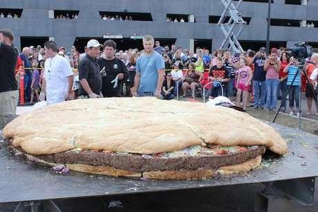 Una hamburguesa gigante con queso y tocino, de tres metros (10 pies) de diámetro y 914 kilogramos (2.014 libras) de peso, atrae la atención de numerosos curiosos momentos antes de que la sirvieran en el Casino-Hotel Black Bear cerca de Carlton, Minnesota.