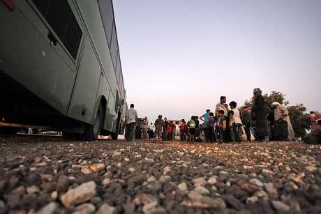 Refugiados sirios recién llegados forman fila para ser llevados por un autobús militar al Campamento de Refugiados de Zaatari en la ciudad de Mafraq (Jordania)