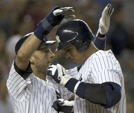 New York Yankees runner Derek Jeter congratulates batter Alex Rodriguez (R) at home plate after his two-run home run against the Tampa Bay Rays in the eighth inning of their MLB American League game at Yankee Stadium in New York, September 14, 2012.