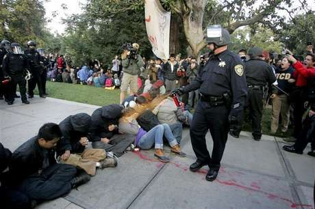 """A University of California Davis police officer pepper-sprays students during their sit-in at an """"Occupy UCD"""" demonstration in Davis, California November 18, 2011."""