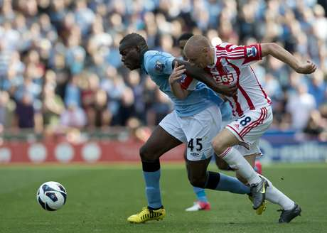 Stoke City's Andy Wilkinson (R) vies for the ball against Manchester City's Italian forward Mario Balotelli (C) during the Premiership football match at the Brittania Stadium in Stoke on September 15, 2012.