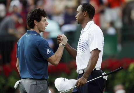 Rory McIlroy, left, of Northern Ireland, and Tiger Woods shake hands on the 18th green after completing the first round of the Tour Championship golf tournament, Thursday, Sept. 20, 2012, in Atlanta. Woods finished 4-under 66 to earn him a share of the lead.