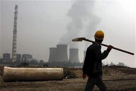 A coal-burning power station can be seen behind a migrant worker as he walks carrying his shovel on the construction site of a water canal, being built in a dried-up river bed located on the outskirts of Beijing October 22, 2010.