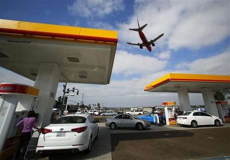 Consumers purchase gasoline at a gas station as a plane approaches to land at the airport in San Diego, California October 8, 2012.
