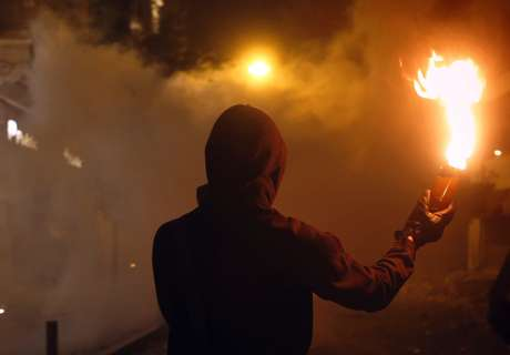 """A hooded protester holds a Molotov cocktail as he taunts riot police during a violent demonstration in Syntagma square in central Athens November 7, 2012. Nearly 100,000 Greeks waving flags and chanting """"Fight! They're drinking our blood"""" packed the square outside parliament as lawmakers neared a vote on unpopular budget cuts and labor reforms."""