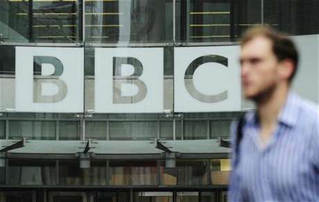A pedestrian walks past a BBC logo at Broadcasting House in central London October 22, 2012.