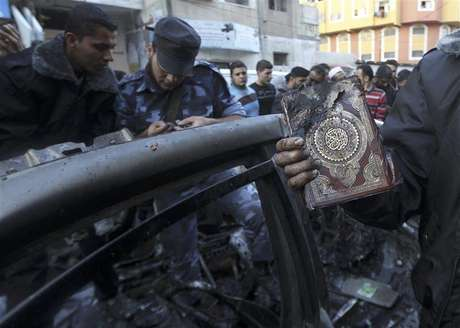 A man holds a copy of Koran after an Israeli air strike on a car of Hamas's military chief in Gaza City November 14, 2012.