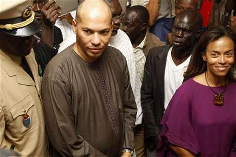 Karim Wade (2nd L) and Sindiely Wade (R), children of Senegal's former President Abdoulaye Wade, prepare to vote during presidential elections in the capital Dakar February 26, 2012.
