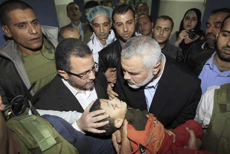 Senior Hamas leader Ismail Haniyeh (C) and Egypt's Prime Minister Hisham Kandil (2nd L) touch the body of a Palestinian boy during a visit to a hospital in Gaza City November 16, 2012.
